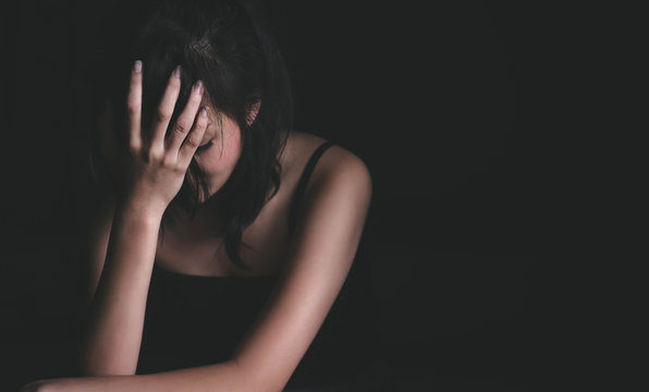Sad depressed woman suffering from family life. women sitting in dark room and right palm touching her face feeling worry. Young beautiful women thinking how to solve problem.