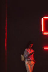 Beautiful elegant Asian woman standing at night club by the red neon light and typing on her cell phone.