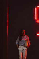 Portrait of beautiful elegant Thai woman standing at night club by the red neon light.