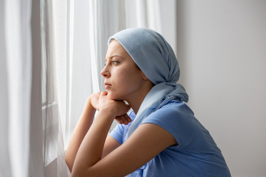 Thoughtful young girl suffering from ovarian cancer, wearing blue headscarf and looking through the window in medical center