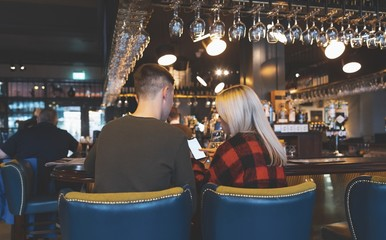 Couple discussing on mobile phone at bar counter