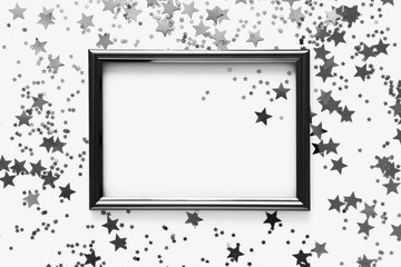 Holiday background. Black photo frame and black stars on white background. Flat lay, top view, copy space