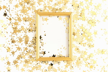 Christmas elegant composition. Photo frame, golden stars decorations on white background. Christmas, New Year, birthday concept. Flat lay, top view, copy space