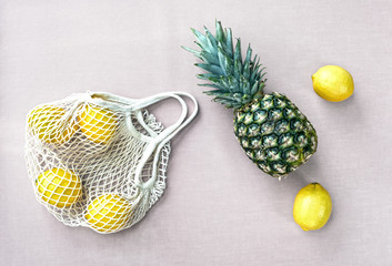Mesh shopping bag with lemons and pineapple on pastel pink canvas background.