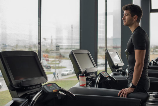 Man standing on a running machine looking out of a window