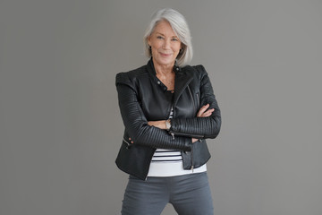 Modern senior woman in leather jacket on isolated grey background