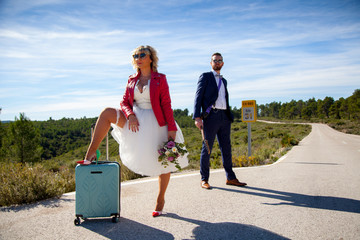 A woman dressed as a bride, with a red jacket, a bouquet and a suitcase waiting next to a man dressed in a suit and an electric guitar on a lonely road.