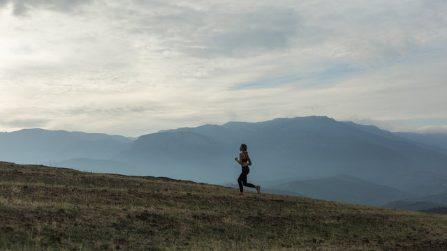 Slim girl wearing black sport outfit is jogging in mountains, beautiful landscape, cloudy sky, foggy hills.