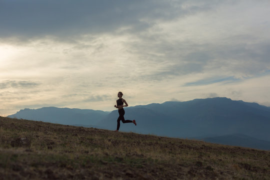 Slim girl wearing black sport outfit is jogging in mountains uphill, beautiful landscape, cloudy sky, foggy hills, sun is shining