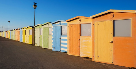 A row of twenty colorful beach huts with a diminishing perspective on a promenade, Seaford, Sussex, UK