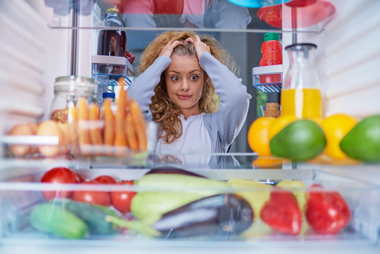 Confused woman choosing what to eat. Hands on head. Picture taken from the inside of fridge full of groceries.