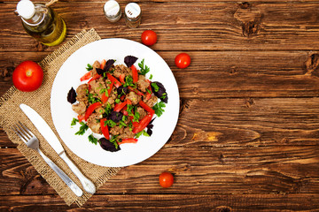 Fried liver with onion and tomatoes on wooden background