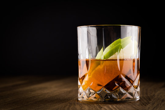 Whiskey with Slices of Green Apple on Wooden Table and black background. Copy Space