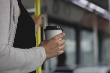 Woman having coffee while travelling in train