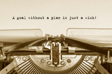 A goal without a plan is just a wish!  typed words on a vintage typewriter with vintage background.