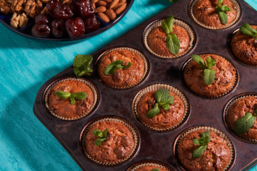 freshly made muffins with mint served to the table with dates almonds and walnuts