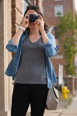Woman clicking photos with camera in the city