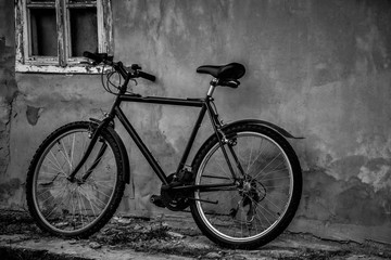Black bicycle parking at the old house in black and white.