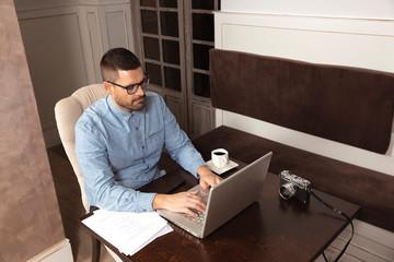Hombre de negocios escribiendo con su ordenador personal en cafetería