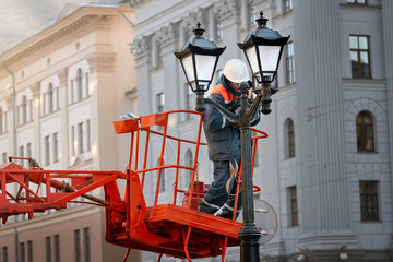 Worker during work on replacement of old ceiling light cover with new ones. Professional service for repair and maintenance of street lighting. Dangerous work at height. Modernization of street lamps Fotomurales