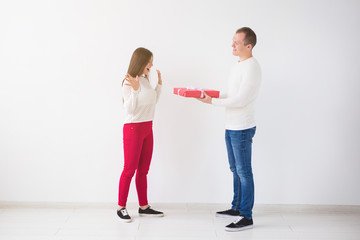 People, christmas, birthday, holidays and valentine's day concept - Handsome man is giving his girlfriend a gift box on white background