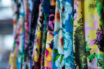 Colorful fabrics hanging and lined. Fabrics with different patterns and colored rows. Wide selection of different color textile.