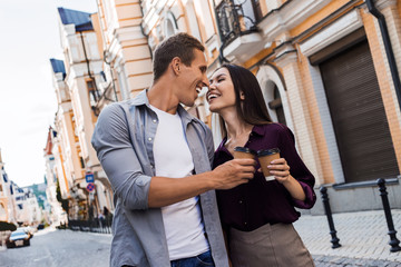Positive multiracial couple walking together, stroll during weekends, drink takeaway coffee, stand near fence, have pleasant talk with each other, Valentine's Day. People and lifestyle concept