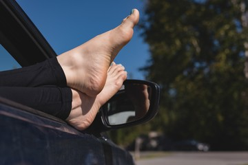 Woman relaxing with feet up in a car