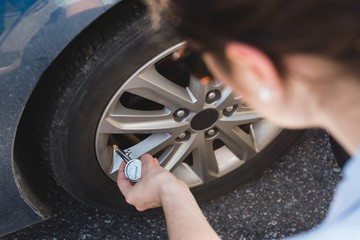 Woman checking a tyre on a road