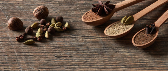 Cardamom, cloves, nutmeg, star anise, allspice. Different types of whole Indian spices in wooden...