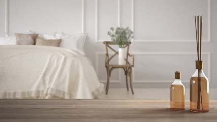 Wooden table top or shelf with aromatic sticks bottles over blurred vintage classic bedroom with soft bed full of pillows and blankets, white architecture interior design
