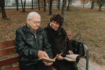 Senior couple reading books in park