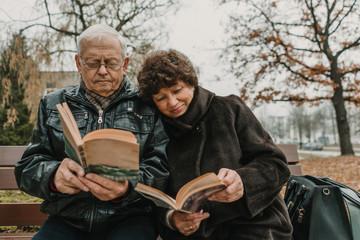 Senior couple reading books in park