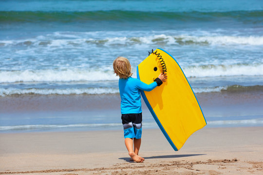 Baby boy - little surfer run with bodyboard to sea for riding on waves. Active family lifestyle, kids watersport lessons, swimming activity in adventure surfing camp. Beach summer vacation with child.