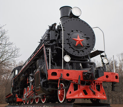 Old black and red soviet steam locomotive with red star in front, front view