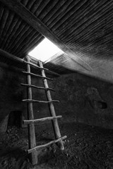 Wooden Ladder out of a Kiva with rays of light pouring in- timeless monochrome