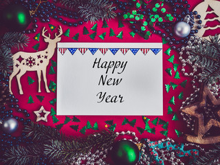 Colorful New Year decorations, silver beads, branches of the Christmas tree, drawing in a notebook on a red surface. Top view, close-up, flat lay. Greeting card