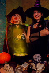 Picture of smiling young witches in black hats with book and magic cauldron at table with pumpkin and skulls