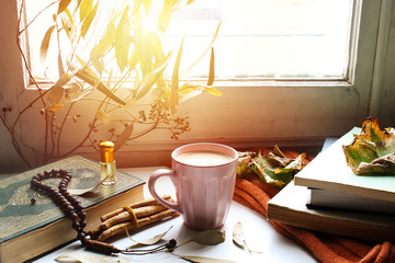Autumn still life for muslim tradition m. cup of coffee,  orange scarf and maple leaves, holy book quran and rosary, siwak, oud perfume  on wooden background. the concept of cozy autumn.