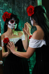 Photo of witch girl with white face with red flower