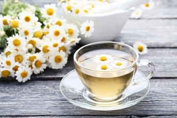 Cup of tea with chamomile flowers on grey wooden table