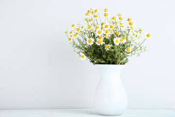 Bouquet of chamomile flowers in vase on grey background