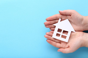 Female hands holding paper house on blue background