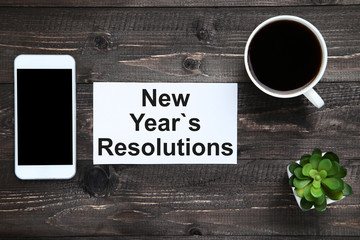 New year resolutions on sheet of paper with smartphone and cup of coffee