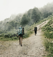 Two hikers walking on the path in mountains.
