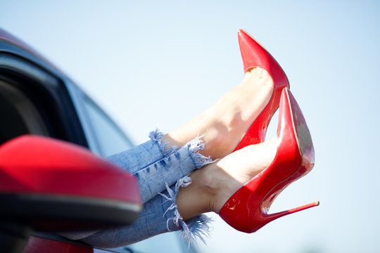 Image of girl's legs in red shoes sticking out of red car window