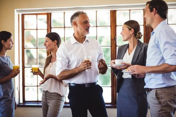 Business people interacting while having food and drink