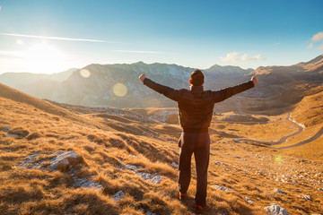 Hiker standing on top of a hill with raised hands