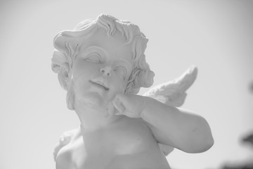 Angel Statue. Portrait of an Angel against the sky. Sculpture of a little boy with curly hair. Cultural object in the park. Marble wares