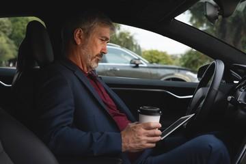 Businessman using digital tablet in a car